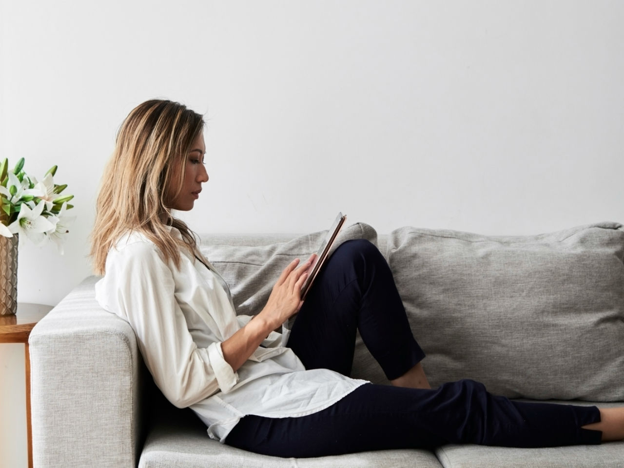 A woman sitting on a couch, using a tablet
