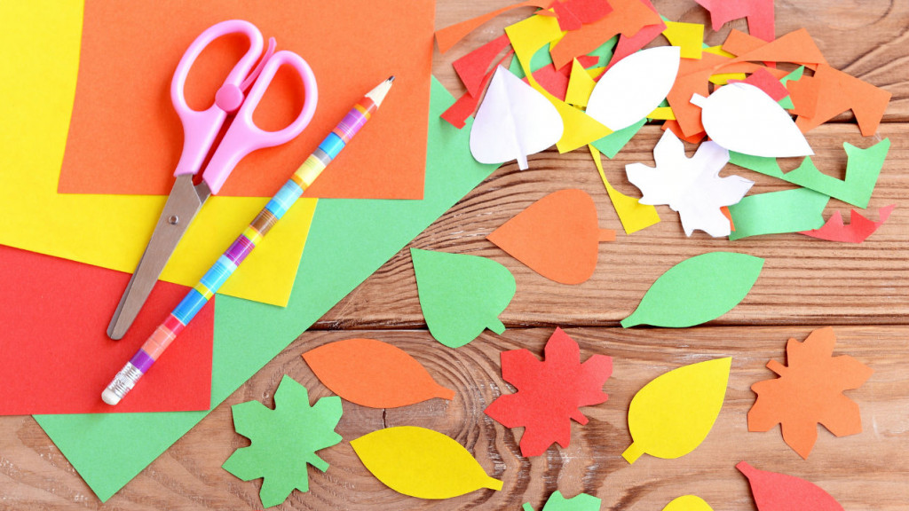A collage of various shapes and colours of leaves placed on the table along with art supplies