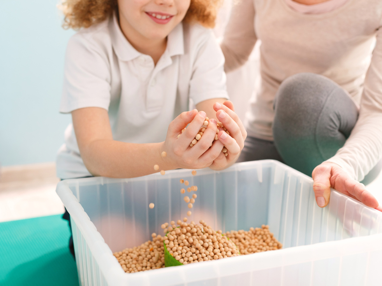 Boy playing with chickpeas during his sensory integration therapy