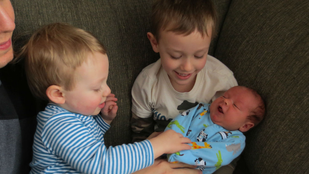 a newborn baby in his brother's lap as the mom and another brother looks