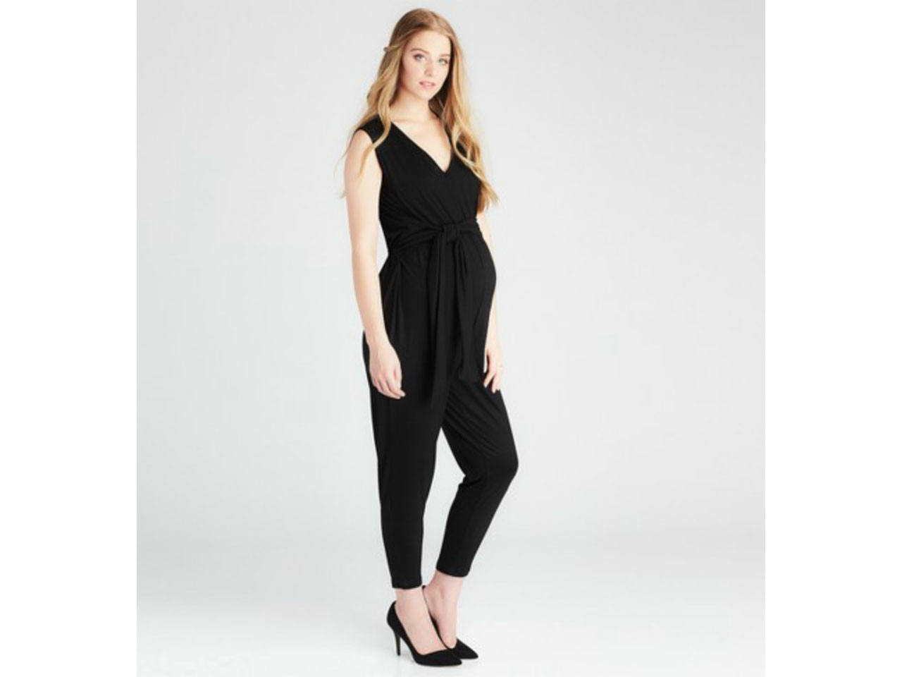 A pregnant woman wearing a black maternity jumpsuit