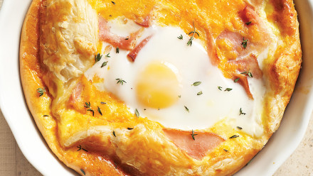 puff pastry in a pie dish covered with egg, ham and cheese