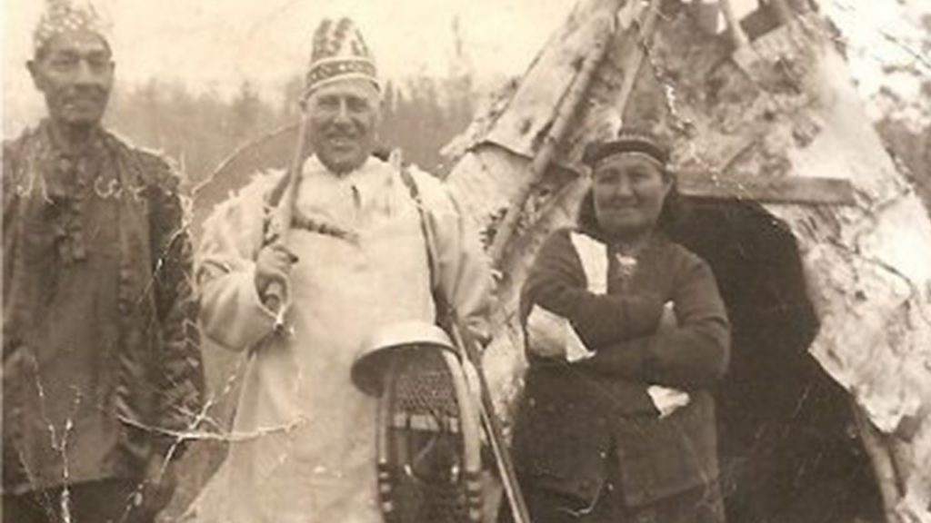 Old photo scan of First Nations people standing outside a teepee