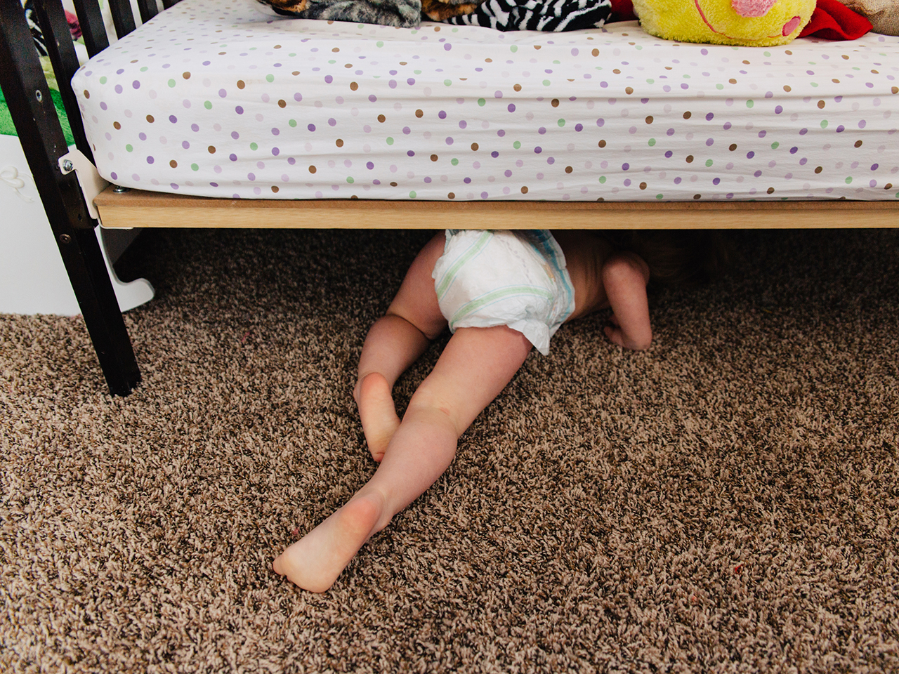 Small child in diaper crawling under bed