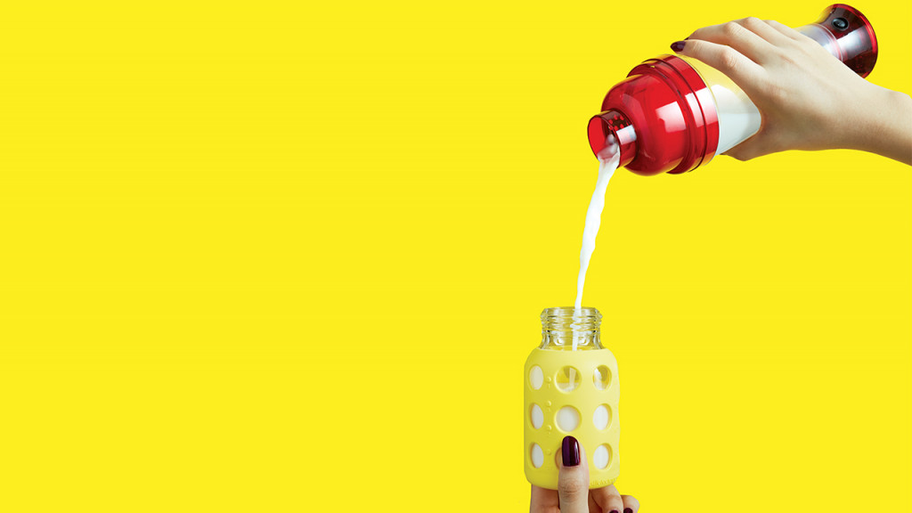 Photo of hands pouring baby formula from a cocktail mixer into a bottle