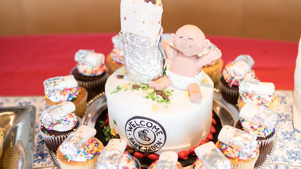 "Photo of the cake showing a baby sitting next to a burrito and the Chipotle logo with the words changed to ""Welcome Baby Jaden"""
