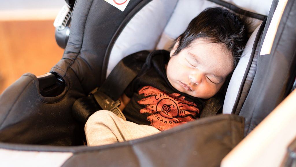 Baby Jaden sleeping in his carrier wearing a Chipotle shirt
