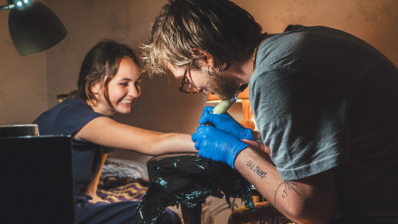 Woman getting a tattoo on her arm