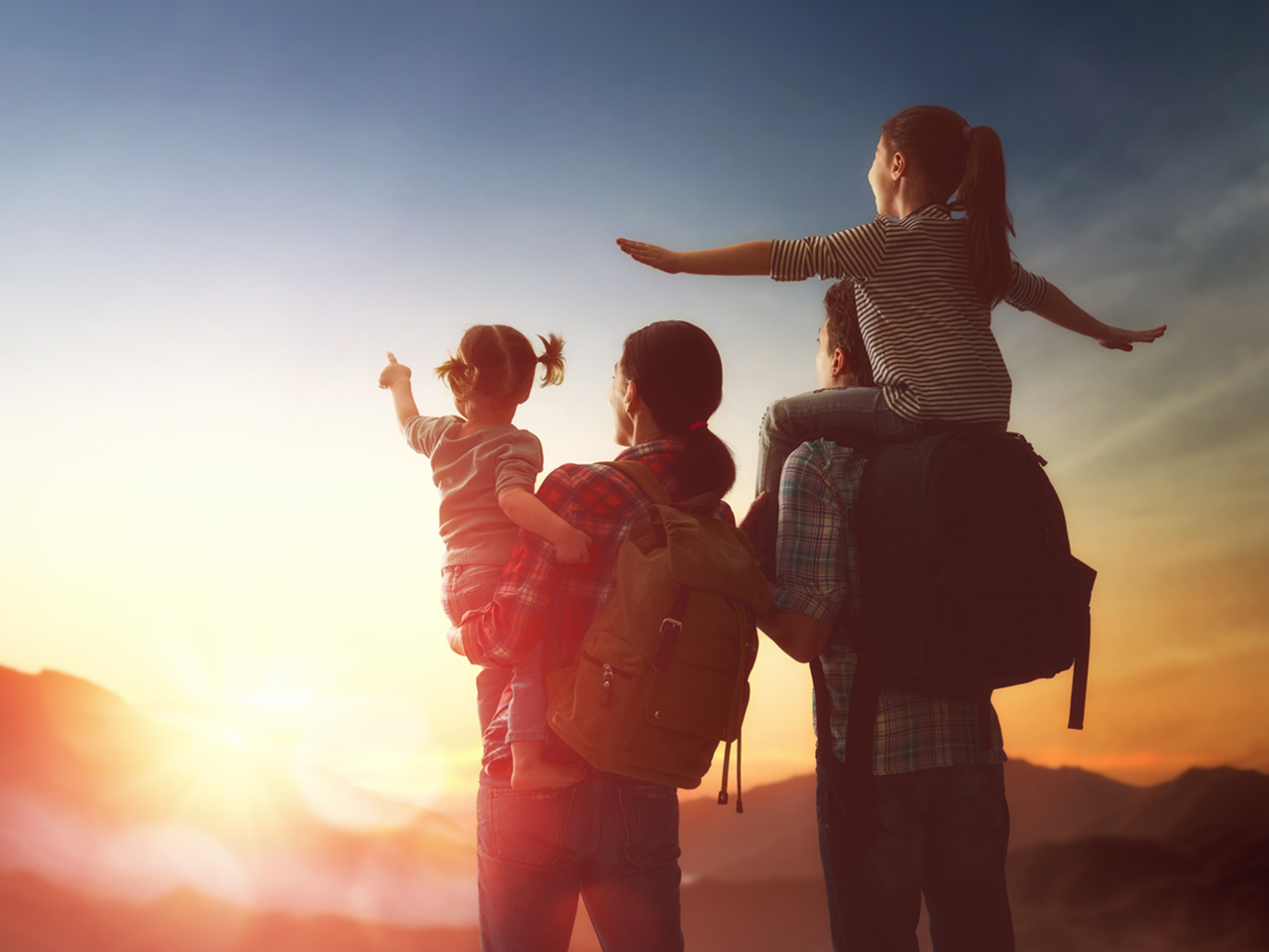 Happy family travelling with two children, staring at the sunset