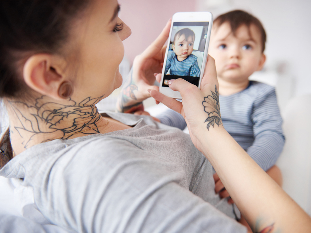 Mother taking a photo of her baby