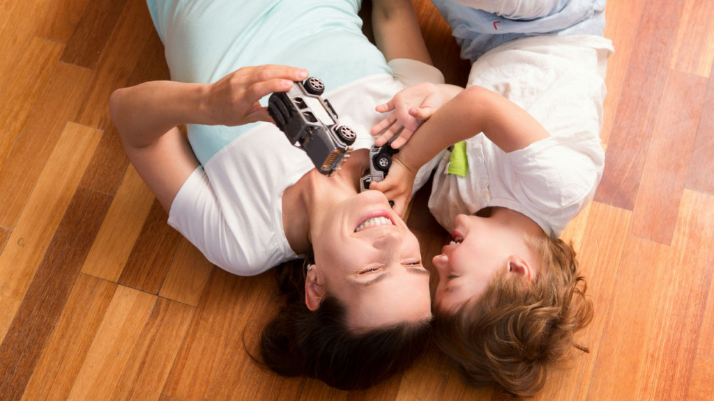 A mother and daughter lying on the floor and playing with a car
