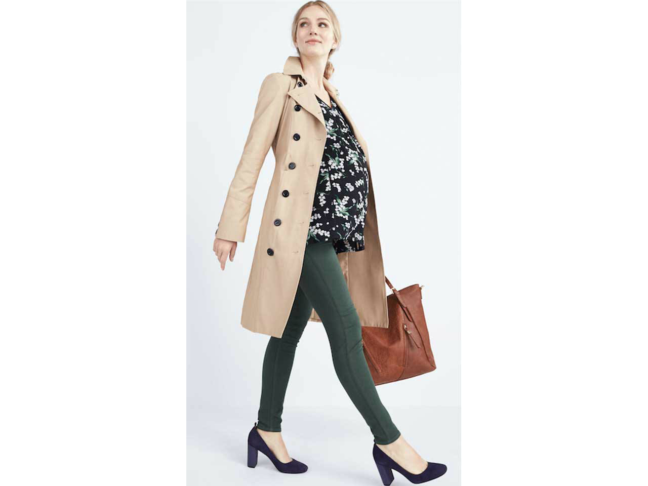 A woman wearing maternity printed top, green maternity jeans and a beige coat