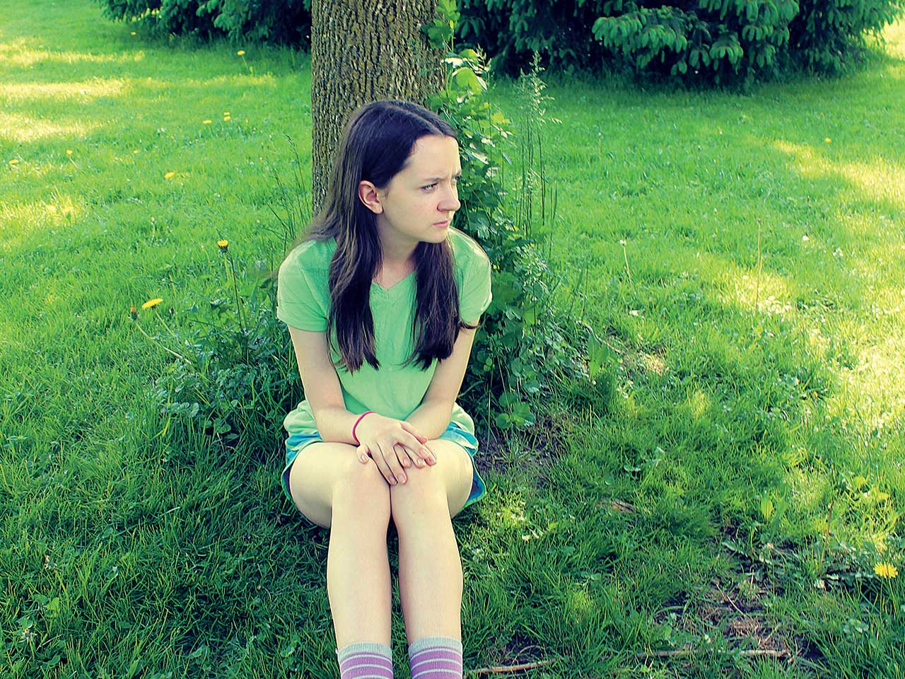 Teenage girl upset and sitting against the tree
