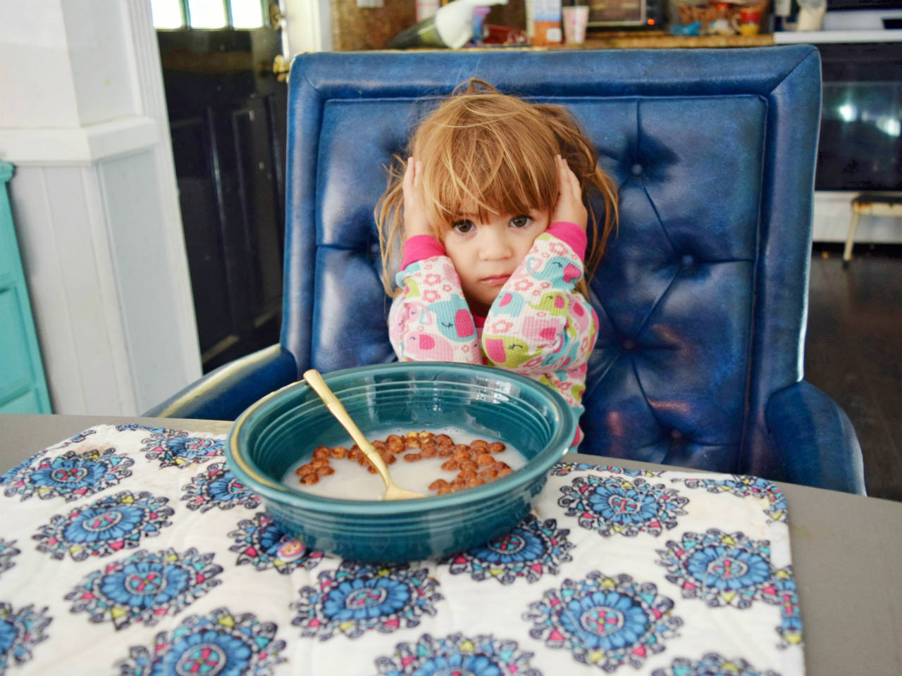 A little girl sitting in front of a half empty cereal bowl with her hands covering her ears