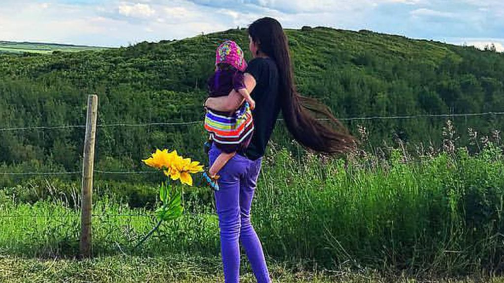 Andrea holding her daughter looking out at a grassy hill