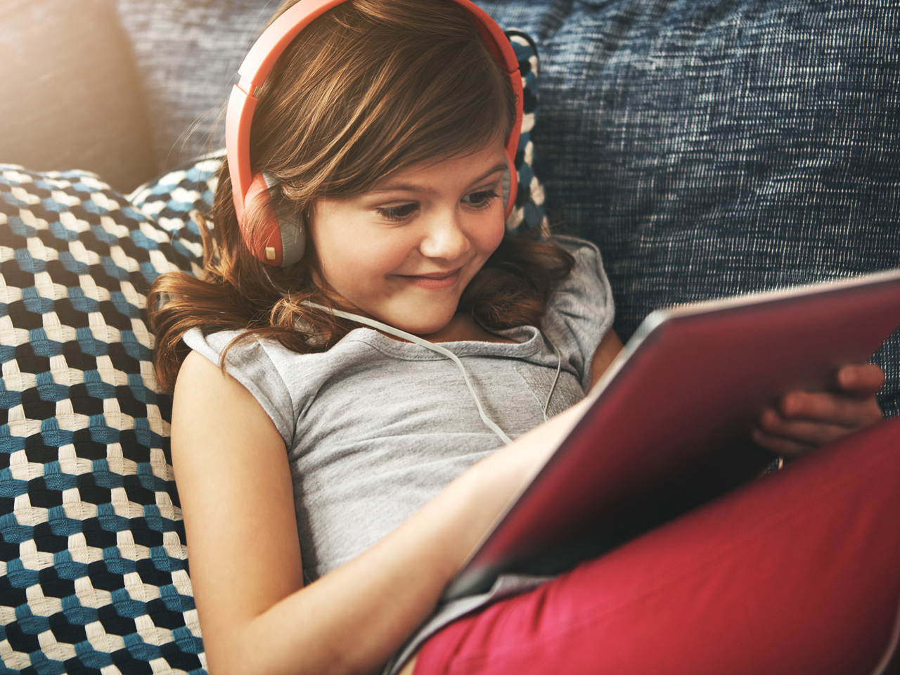 Little girl on the couch with a tablet and headphones, looking engaged