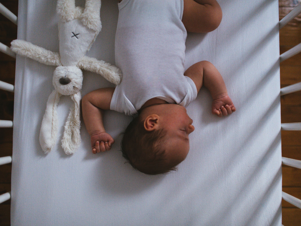 Baby sleeping in crib with stuffed rabbit