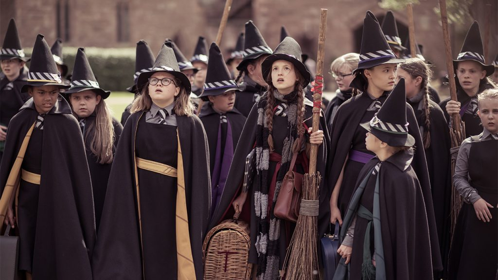 Promo image for The Worst Witch showing a bunch of kids in witch outfits holding brooms