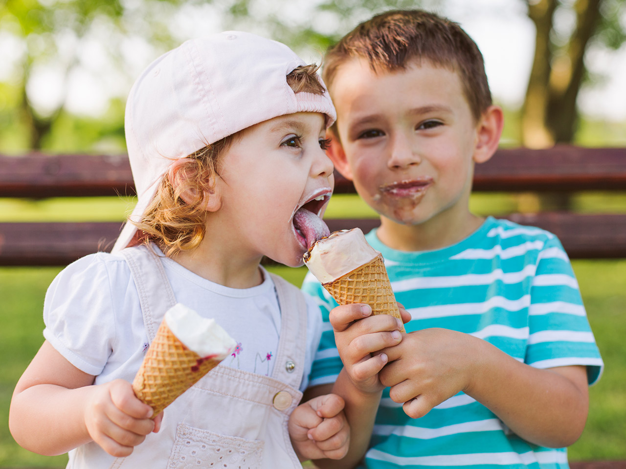 Cute little boy shares ice cream with his sister