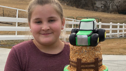 12-year-old Addie Branham holding a tiered tractor cake that she created