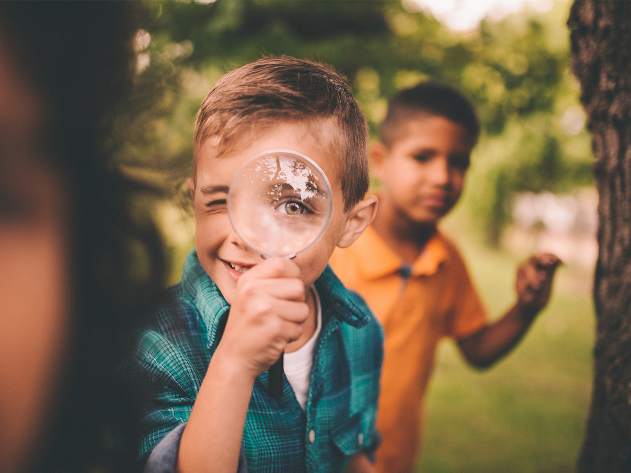 kid with magnifying glass and friend looking behind him