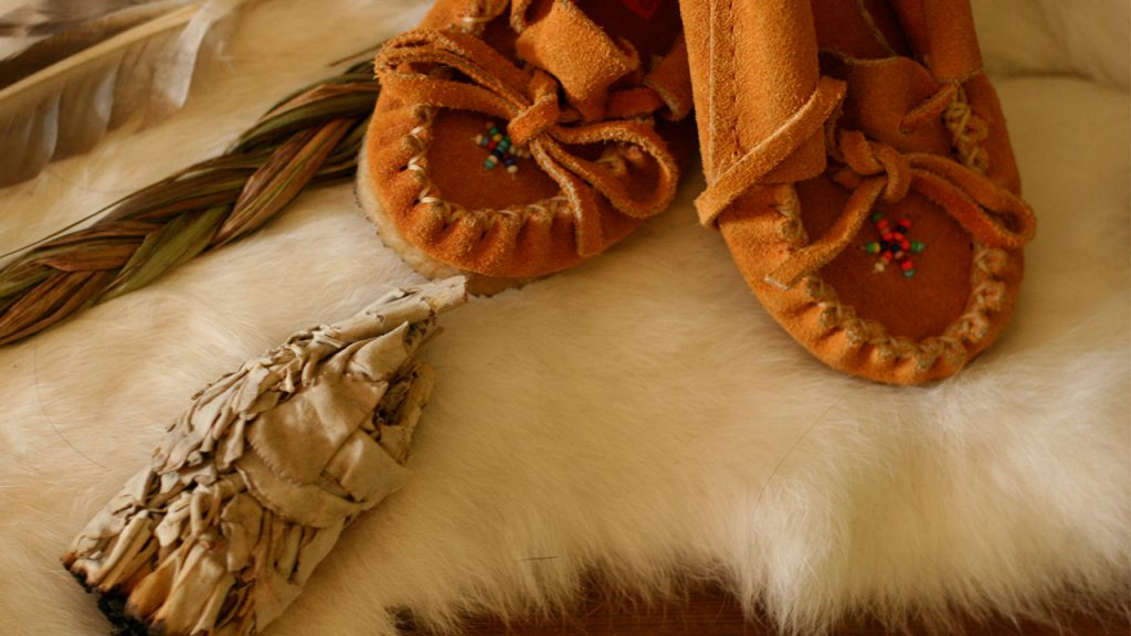 mocassins and a smudge stick on a fur pelt