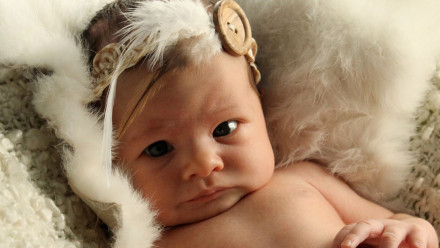 Baby wearing a feathered headband