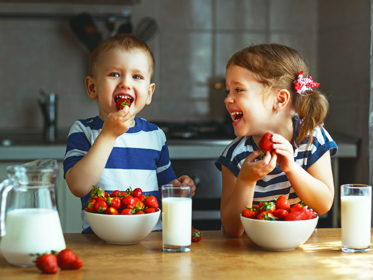 Two kids eating strawberries and milk
