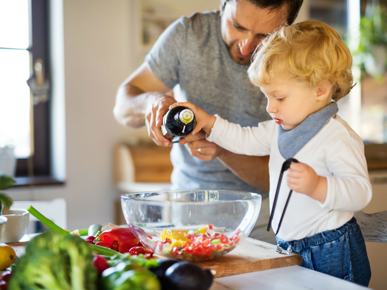 toddler cooking with parent