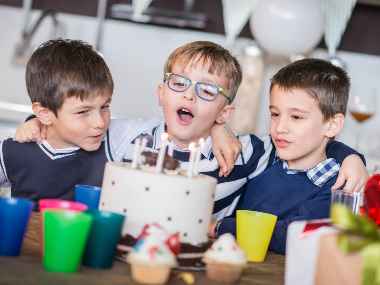 Three boys with a birthday cake at a birthday party