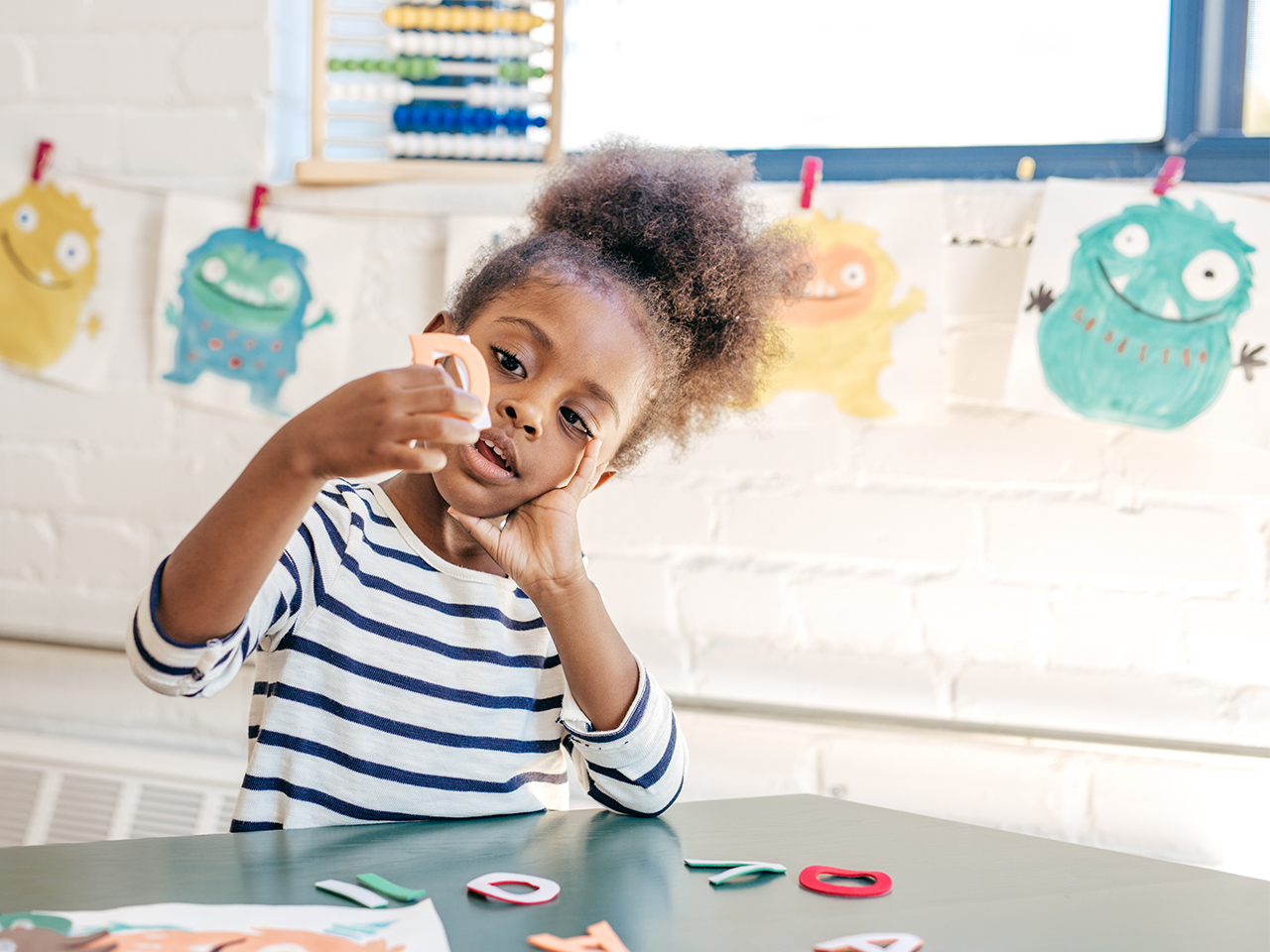 A little girl at preschool playing with letters at a table