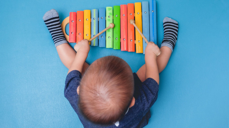 baby playing with a xylophone