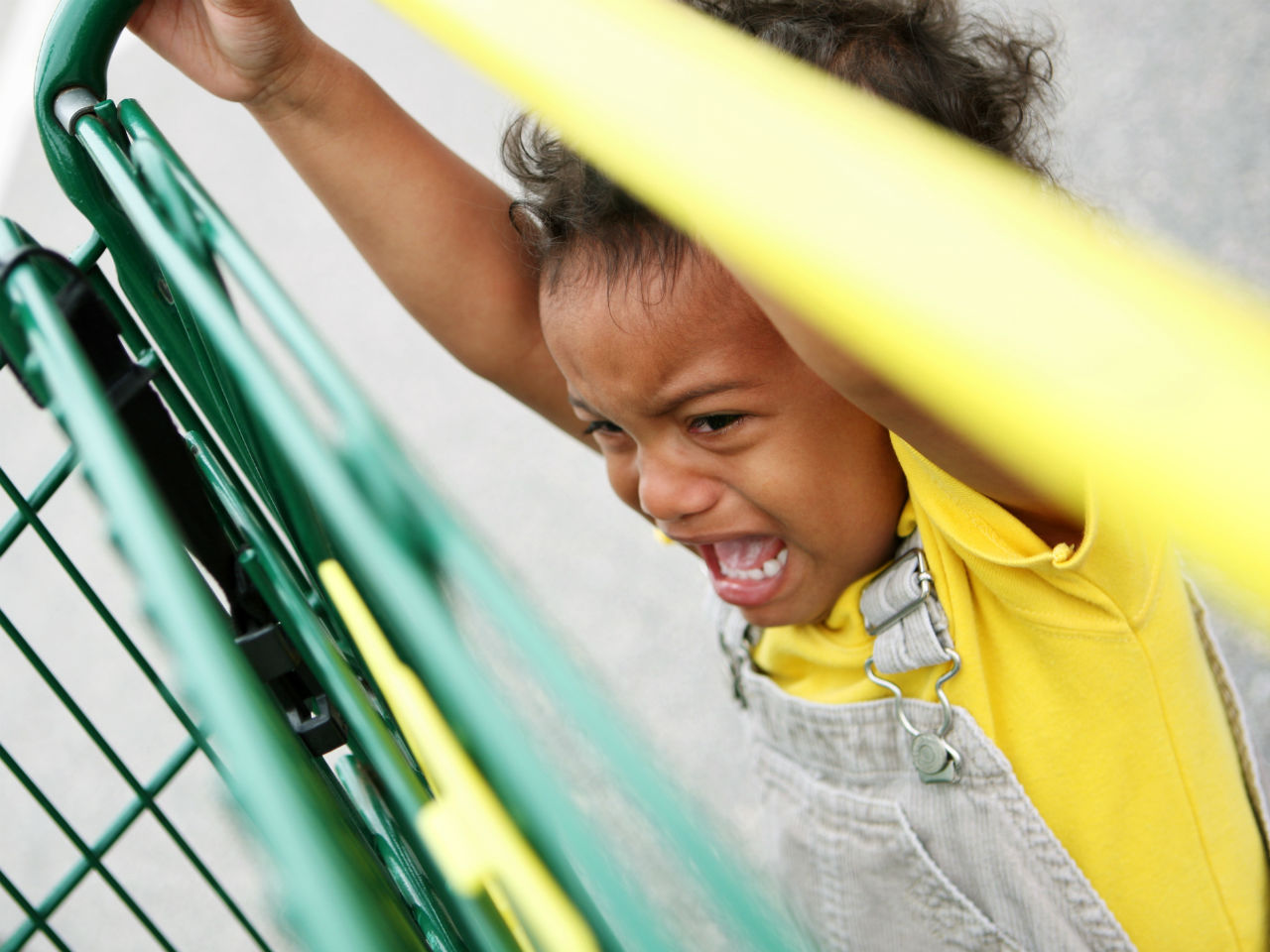 Child crying, hanging off shopping cart