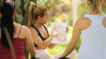 Person teaching a prenatal class outdoors pointing to a printed diagram of a baby in the womb