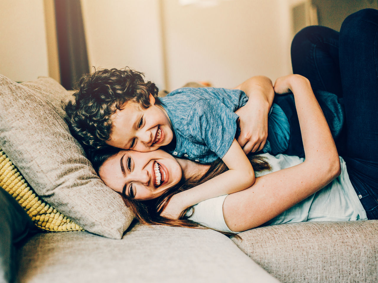 Kid laughing while laying on top of his laughing mom