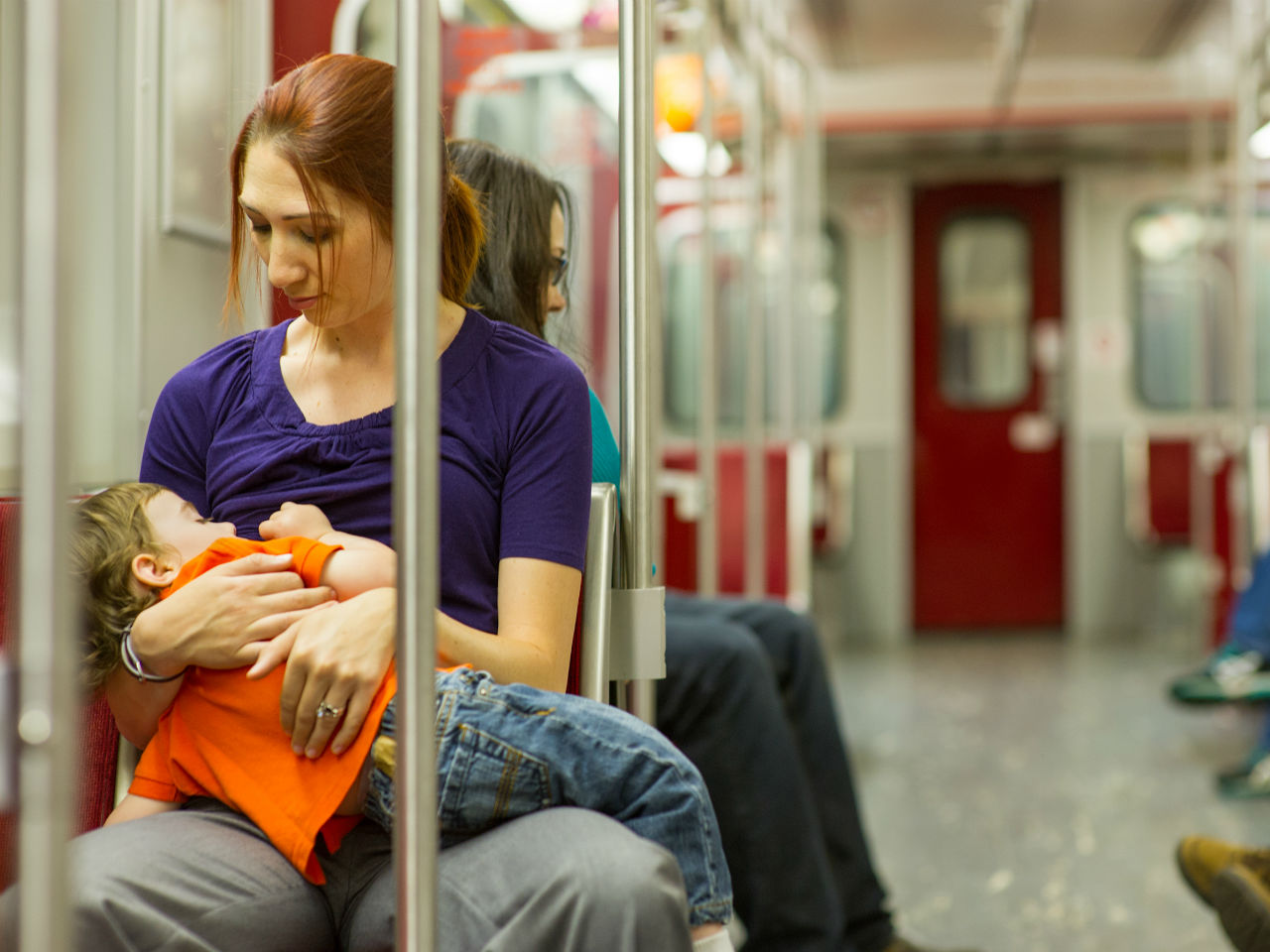 mother breastfeeding her toddler on the subway