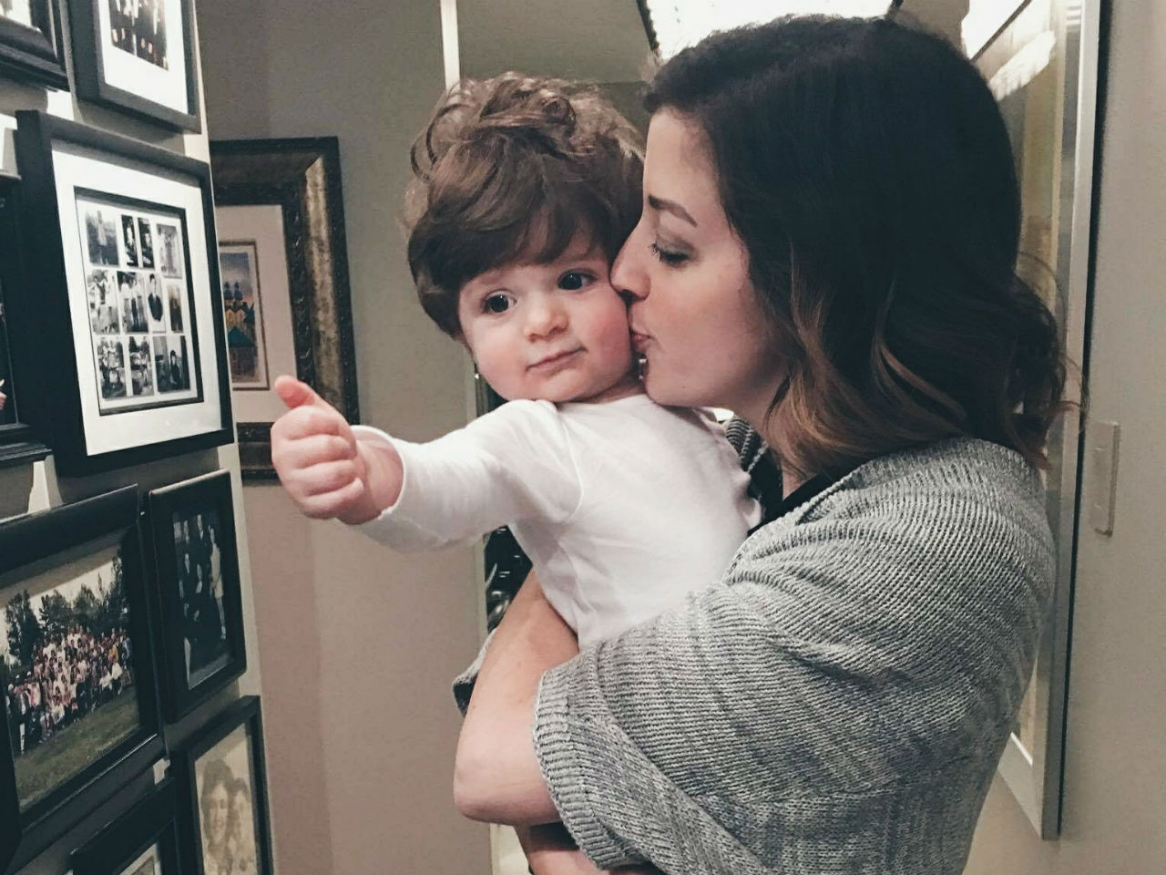 Stephanie Gilman holding her baby and kissing her on the cheek