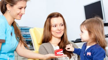 Toddler at the dentist office with her mom