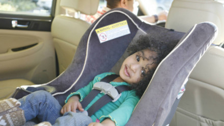 A little girl sitting in a rear facing car seat