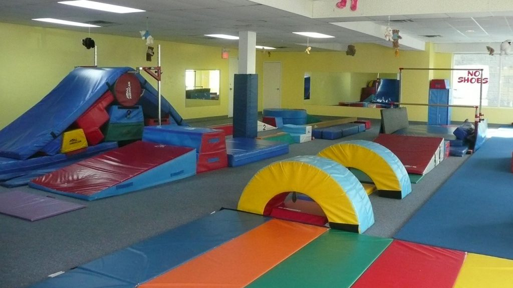 Open floor gym with padded obstacle course, balance beam and uneven bars