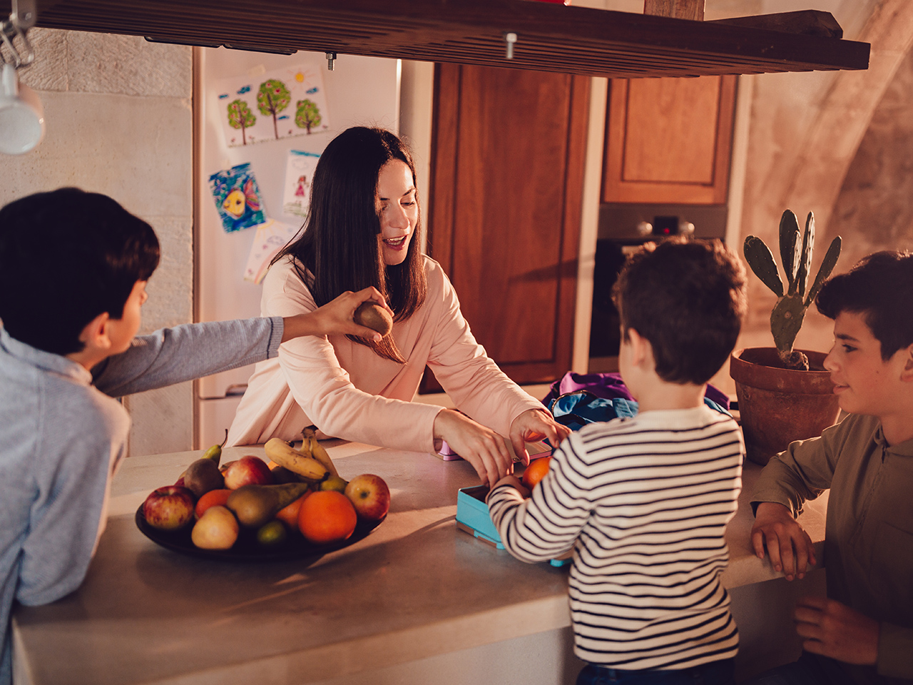 A mom in the kitchen with her boys making their school lunches