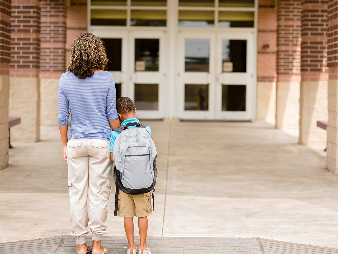 A mom and her son standing outside the school doors