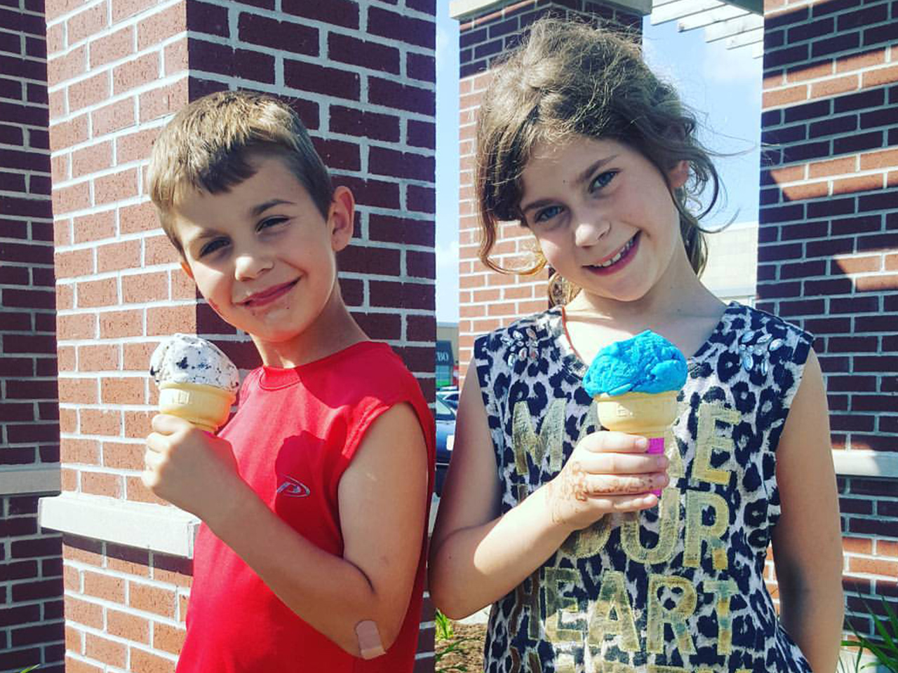 Two kids smiling at the camera while holding ice cream cones