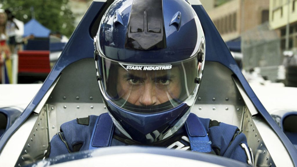 Promo image for Iron Man 2 showing a man in a racecar wearing a helmet that says stark Industries