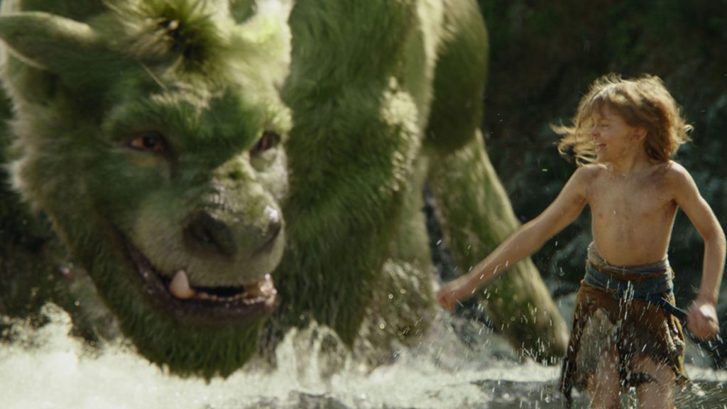 Promo image from Pete's Dragon showing a little boy playing with a big furry dragon