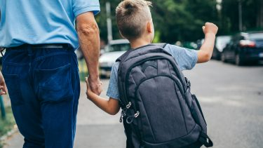 Kid wearing a backpack while walking with an older man
