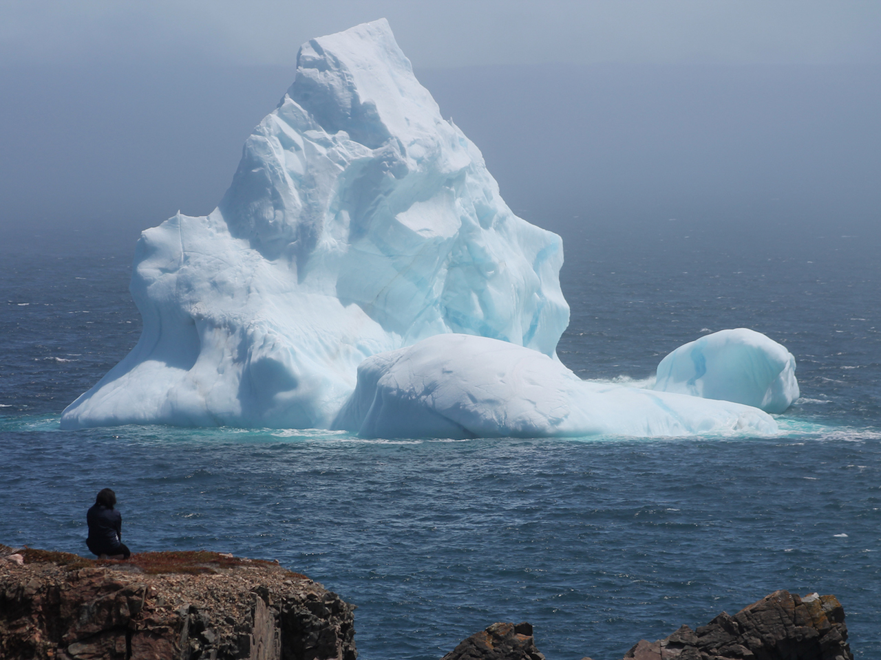 An iceberg as seen from the edge of a cliff.