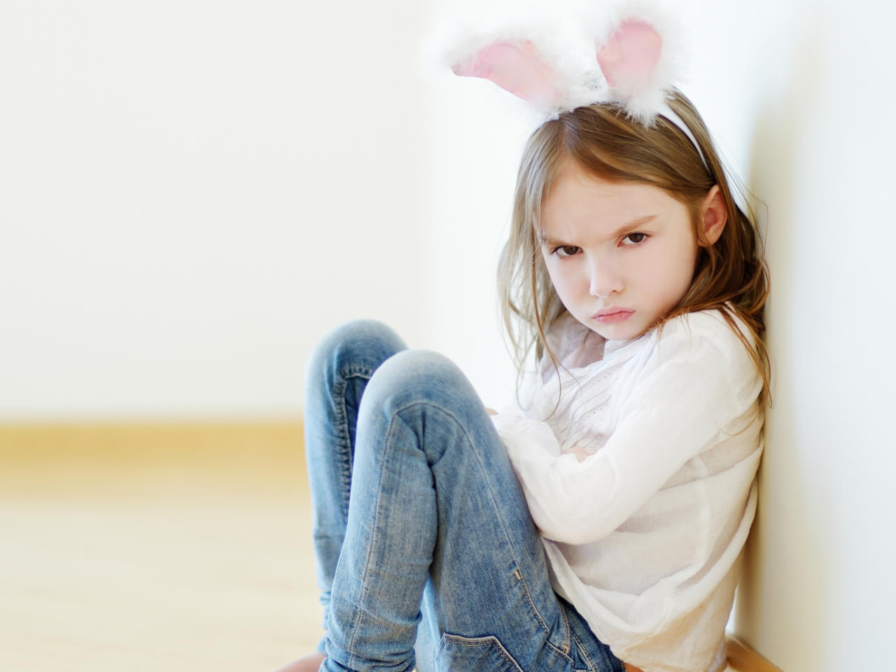 Little girl wearing bunny ears sitting on the floor with her arms crossed