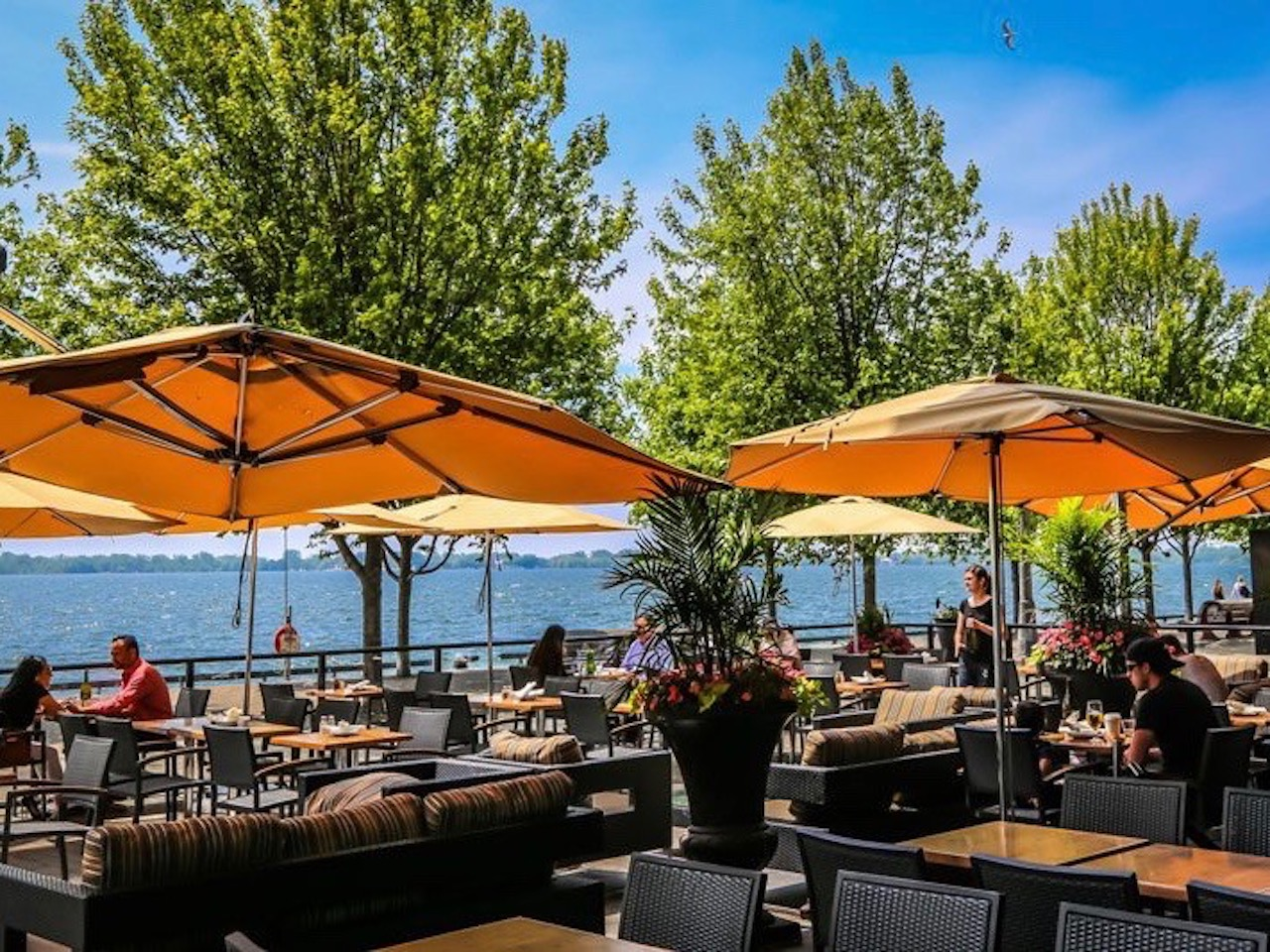 Sunny patio with umbrellas overlooking the lake