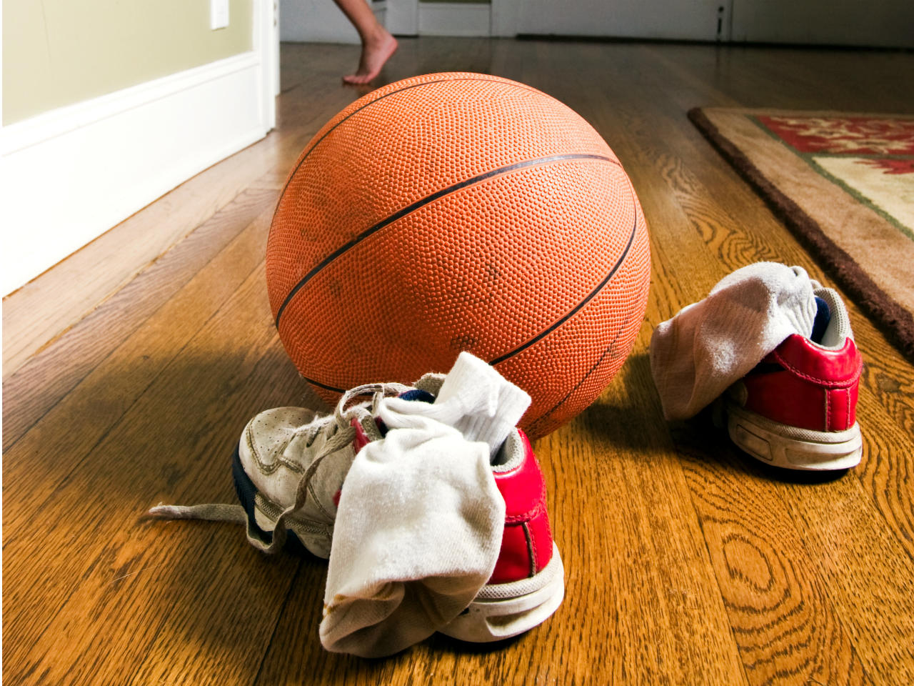 Dirty socks left lying around with sneakers and basketball